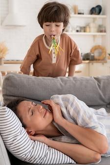台所のソファで疲れ果てた若いお母さんは、騒々しい小さな子供の病気の母親にうんざりしていて、リラックスしてみてください