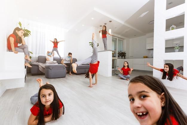疲れ果てた若い親が台所のソファに座って、遊んでいる行儀の悪い大声で小さな子供たちに疲れを感じ、病気のイライラした母親や乳母がソファでリラックスして頭痛に苦しんでいます、 Premium写真