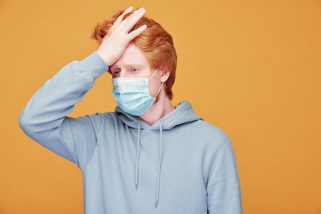 Exhausted young redhead man in mask feeling bad touching forehead while checking temperature, coronavirus concept