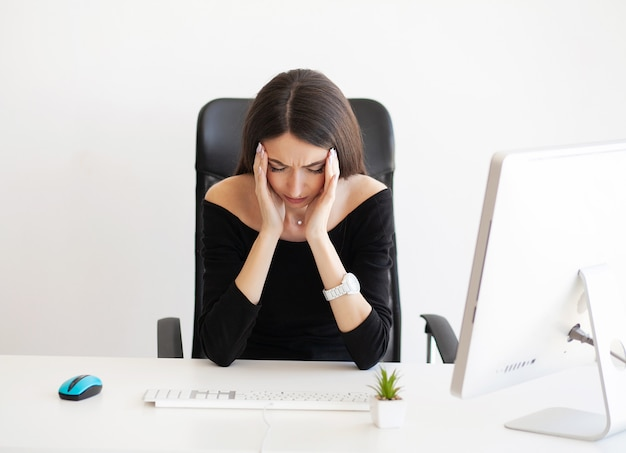 Exhausted young woman feeling pain in head after working on computer.