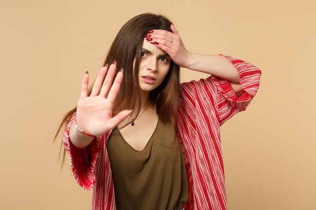パステルベージュの壁の背景に分離された手のひらで停止ジェスチャーを示す額に手を置くカジュアルな服を着て疲れ果てた若い女性。人々の誠実な感情のライフスタイルの概念。コピースペースをモックアップします。