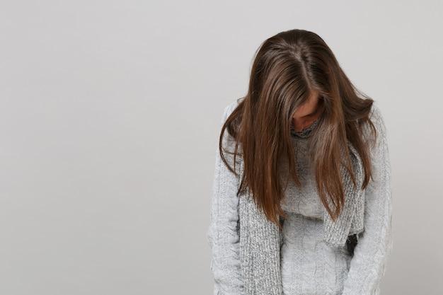 회색 스웨터를 입은 지친 젊은 여성, 회색 배경에 머리를 낮춘 스카프, 스튜디오 초상화. 건강한 패션 라이프 스타일, 사람들은 진심 어린 감정 추운 계절 개념입니다. 복사 공간을 비웃습니다.