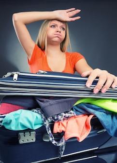 休暇のために荷物を詰める疲れた若い女性