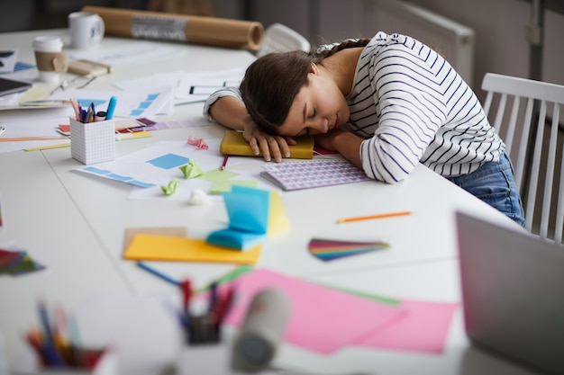 Exhausted young woman sleeping at work