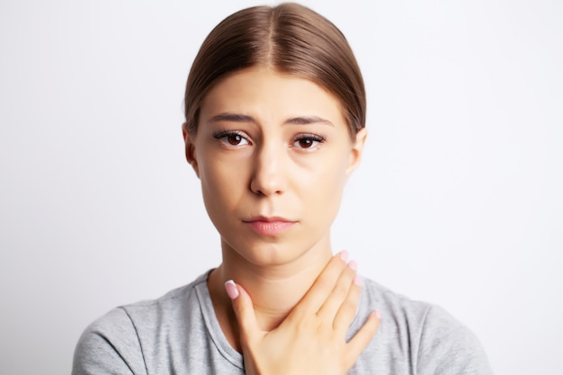 Exhausted young woman suffering from severe neck pain