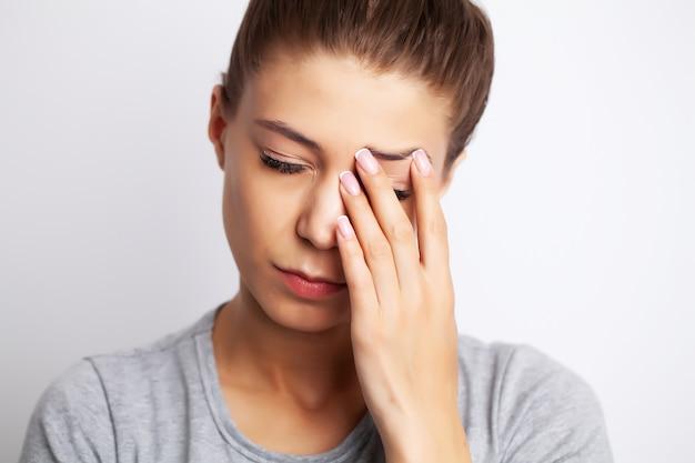 Измученная молодая женщина, страдающая от сильной боли возле глаз