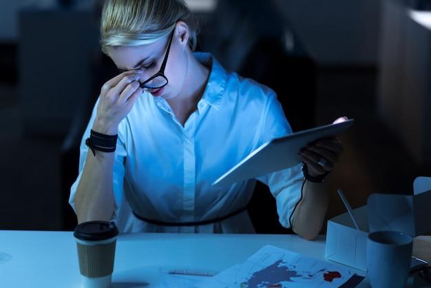 근무 시간이 소진되었습니다. 사무실에 앉아서 태블릿을 들고 프로젝트를 진행하면서 피곤함을 느끼는 피곤한 it 여성