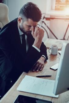 피로. 사무실에 앉아있는 동안 코를 마사지하는 formalwear에서 피곤한 젊은 남자
