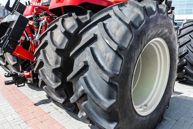농업 기계 전시회 근접 촬영에 거대한 하이패스 타이어가 있는 바퀴 달린 트랙터