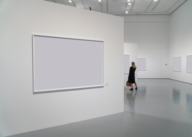 Exhibition room of the gallery with blank pictures and people