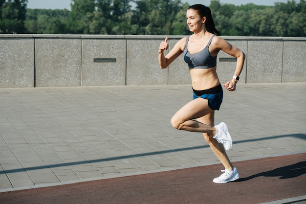 포장 보도 옆 트랙에서 야외에서 빠르게 달리는 신나게 운동하는 여성. 맑고 푸른 하늘 아래 화창한 날. 그녀는 회색 상의와 미니 반바지를 입고 있습니다.