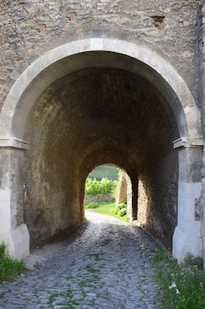 Exit from the castle or fortress. corridor overlooking the green forest. there is no gate, only an arch. covered with rough stone.