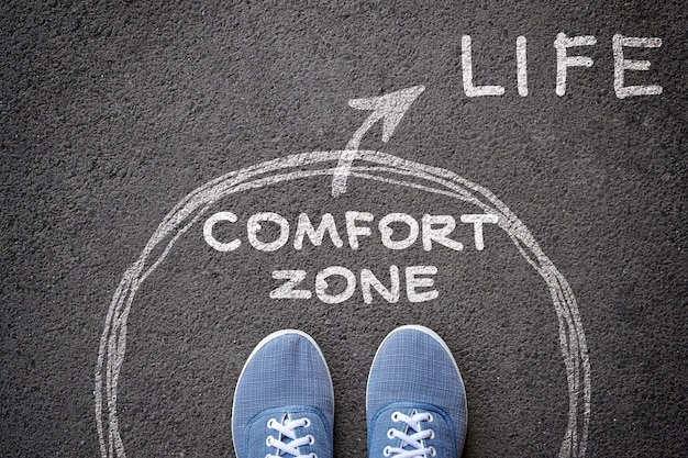 Exit from the comfort zone concept. feet in blue jeans sneakers standing inside circle comfort zone and outward arrow chalky on the asphalt