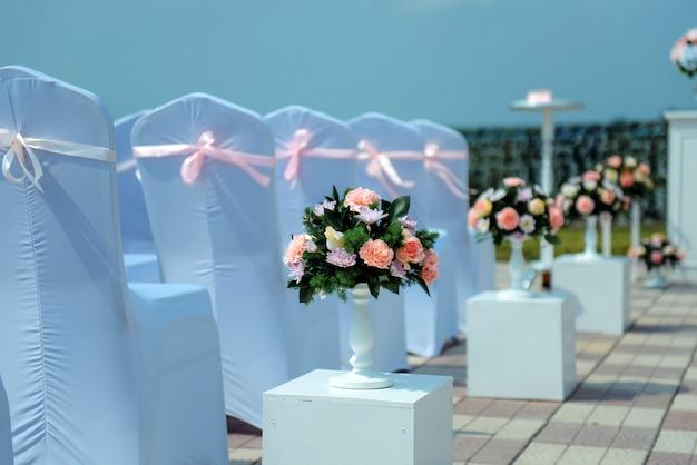 新婚夫婦の退場登録、大空の下での結婚式。座席のゲスト。白いケープ付きの椅子の行をクローズアップ。