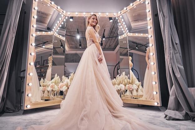 그녀의 결혼식에 대해 종료했습니다. 웨딩 드레스를 입고 신부 가게에 서 있는 동안 웃고 있는 매력적인 젊은 여성의 전체 길이