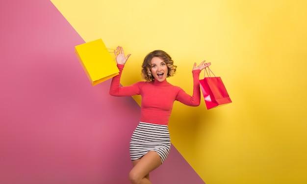 終了した幸せそうな顔の表情、感情的なピンクの黄色の背景、ポロネック、ストライプミニスカート、セール、ディスコ、買い物中毒の買い物袋を保持しているスタイリッシュなカラフルな服で魅力的な女性を終了