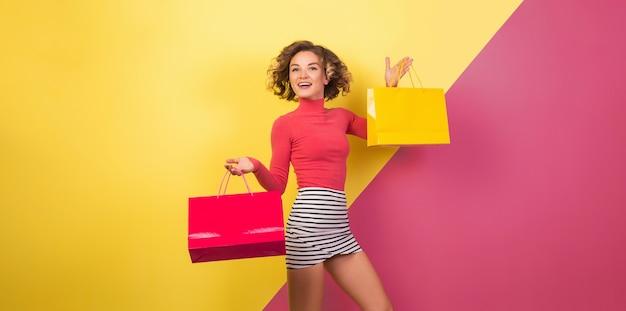 Donna attraente uscita in abito colorato elegante che tiene le borse della spesa con espressione faccia felice uscita, emotivo, sfondo rosa giallo, collo a polo, minigonna a righe, saldi, discout, shopaholic