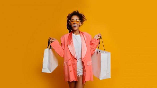 黄色の背景の上に白いショッピングバッグ立って黒人女性を終了しました。トレンディな春のおしゃれな表情。