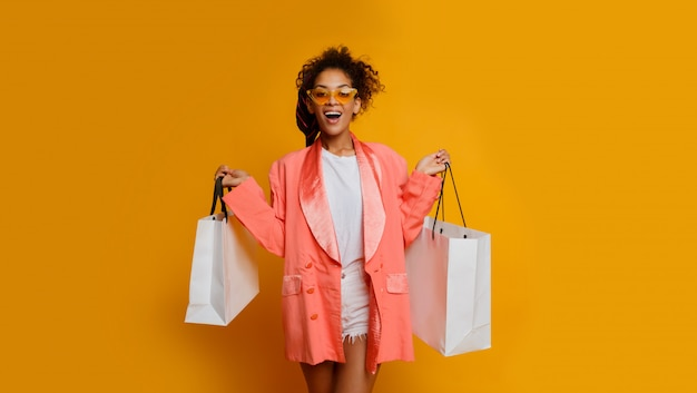 Exited  black woman with white shopping bag standing over yellow background. trendy spring fashionable look.