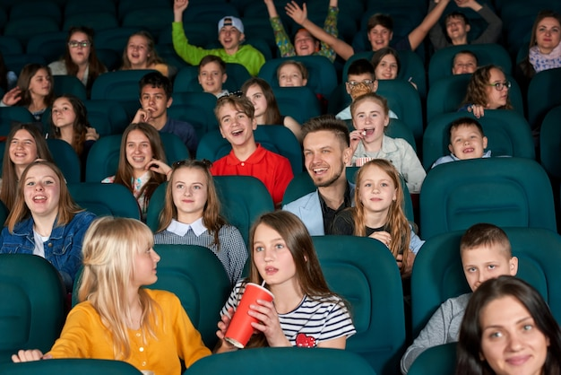 Exited children sitting in the cinema.