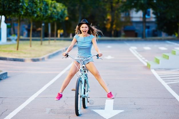 모자, 상단 및 공원, 여행, 초상화, 미소, 복사 공간에서 자전거를 타고 반바지를 입고 곱슬 머리를 가진 귀여운 소녀를 종료했습니다.
