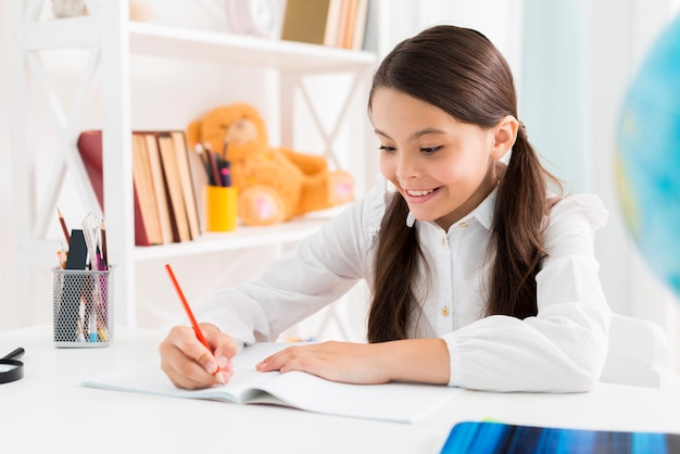 Exited cute schoolgirl in uniform studying at home