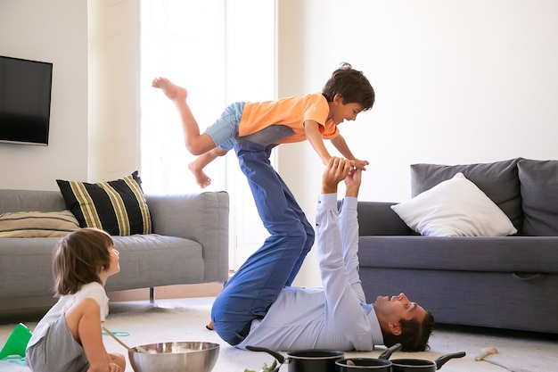 Exited father holding son on legs and lying on carpet. cheerful caucasian boys playing in living room with dad and utensils. cute boy sitting on floor. childhood, holiday and game activity concept