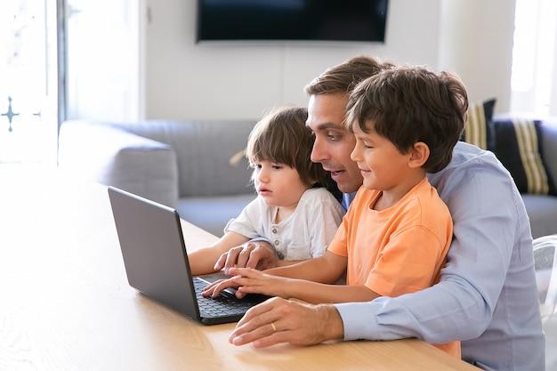 Ушел отец, показывая что-то на ноутбуке маленьким сыновьям. очаровательные кавказские мальчики изучают компьютер дома с помощью любящего отца средних лет. отцовство, детство и концепция цифровых технологий