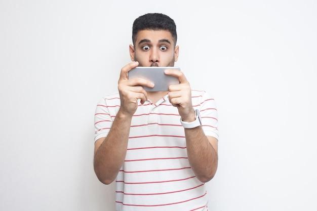 Молодой взрослый человек покидает геймер, одетый в белую футболку, стоя, используя смартфон и играя в мобильную игру с расстроенным лицом и большими глазами, прикрывая рот. крытый, изолированный, студийный снимок, белый фон