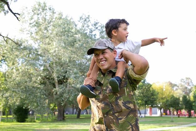 Ragazzino uscito seduto sul collo di papà e indicando lontano. padre caucasico che tiene le gambe del figlio, sorridente, con indosso l'uniforme dell'esercito e passeggiate nel parco. ricongiungimento familiare, paternità e concetto di ritorno a casa