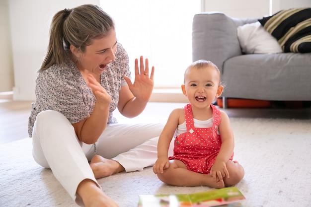 床に座って母親と遊んでいる少女を出ました。彼女の素敵な娘と楽しんで、何かを拍手して叫んでいる陽気なブロンドのお母さん。家族、母性、在宅のコンセプト