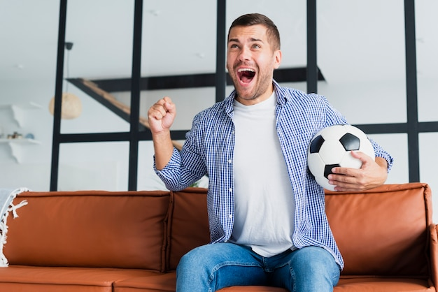 Exited man with football ball on couch