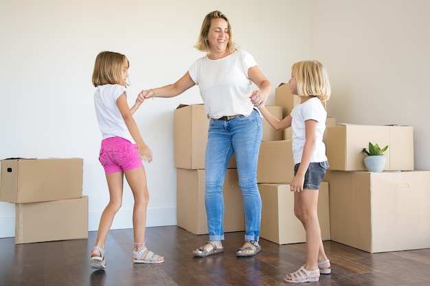 Exited mother standing and holding hands of two girls among unpacked boxes