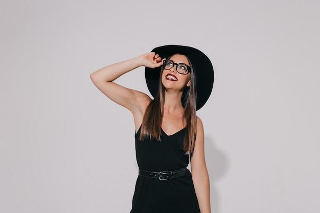 Uscito dalla ragazza felice alla moda che indossa un abito nero e cappello con gli occhiali e alzando lo sguardo con il sorriso