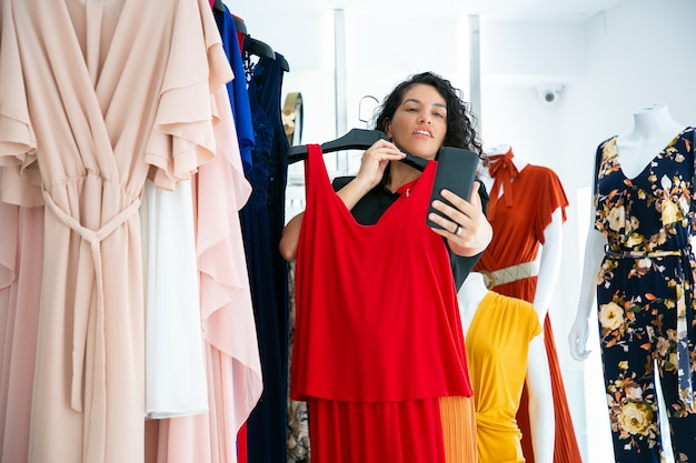 Exited woman shopping in clothes store and consulting friend on cellphone, showing red dress on hanger. medium shot. boutique customer or communication concept