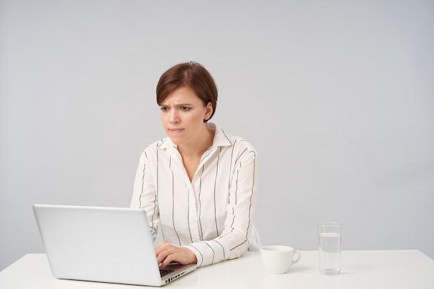 Uscito giovane signora dai capelli castani con taglio di capelli corto alla moda tenendo le mani sulla tastiera e guardando preoccupante lo schermo del suo laptop, seduto su bianco