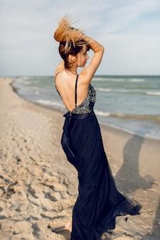 Выходящая изящная женщина в элегантном длинном синем платье дурачится и веселится на тропическом пляже. время отдыха
