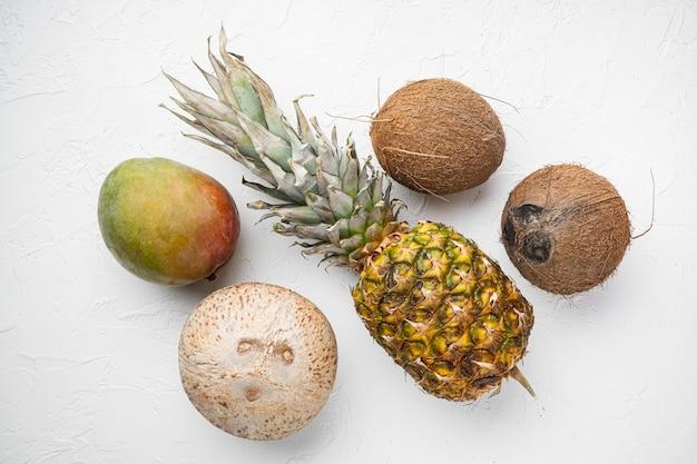 이국적인 열대 과일, 파인애플과 코코넛 세트, 흰색 돌 테이블 배경, 평면도 평면 누워