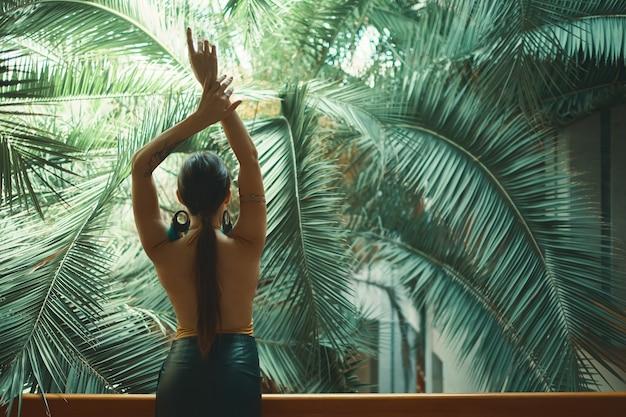 Экзотическая красивая женщина отдыхает на балконе во время своего отпуска
