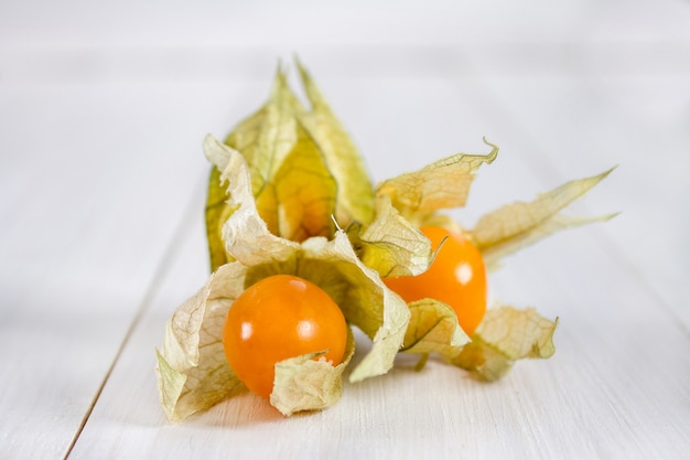 Exotic berries physalis on a white wooden table.