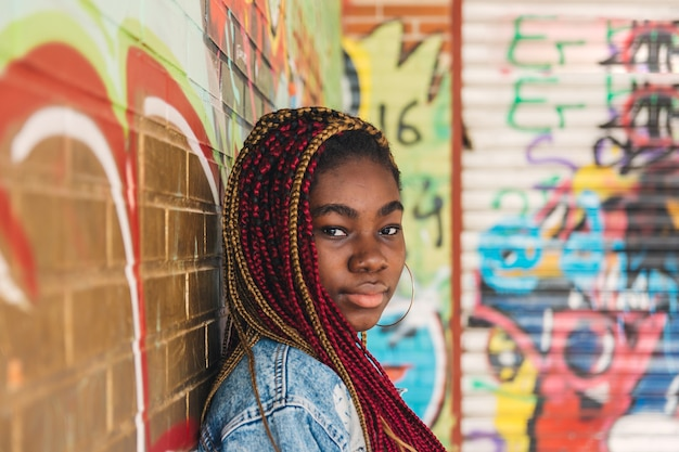 Exotic black girl with colored braids in her hair. leaning on a graffiti wall.
