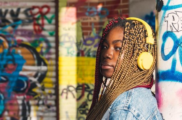 그녀의 머리에 색된 머리 띠와 음악을 듣고 노란색 헤드폰 이국적인 흑인 소녀. 낙서 벽에 기대어.