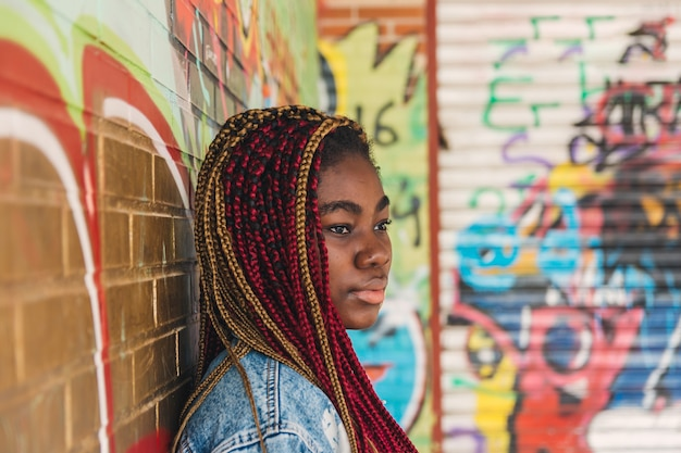 Экзотическая черная девушка с цветными косами в волосах. опираясь на стену с граффити.