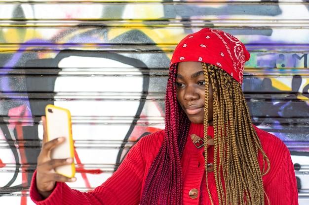 그녀의 휴대 전화로 자신의 사진을 찍는 색 머리 띠와 이국적인 흑인 소녀. 빨간 스웨터와 빨간 머리 스카프를 입고. 낙서 벽에 기대어.