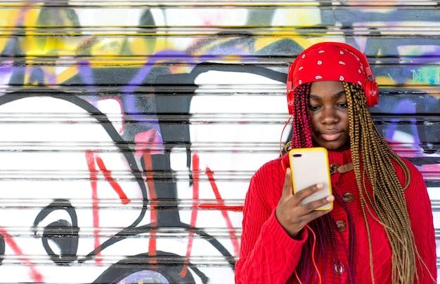 그녀의 휴대 전화를 사용 하여 색된 머리 띠와 이국적인 흑인 소녀. 빨간 스웨터와 빨간 머리 스카프를 입고. 낙서 벽에 기대어.