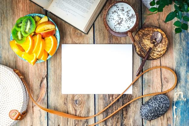Экзотический завтрак с пустой бумагой для копирования. пудинг из семян чиа, тарелка с фруктами и книга на деревянном столе.