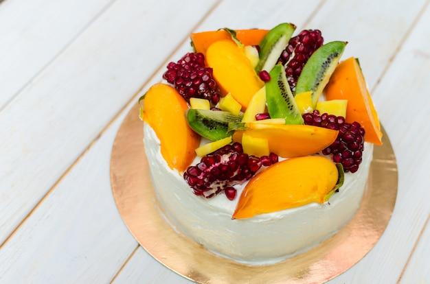 エキゾチックなケーキ。ホワイトクリームとフルーツたっぷりのスポンジケーキ(キウイ、ザクロ、柿、マンゴー)