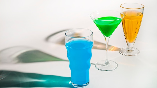 Exotic cocktail in different type of glasses with shadow on white backdrop