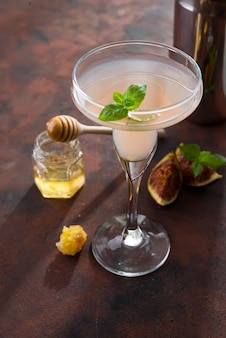 Exotic cocktail and figs, honey on brown stone background , copy space