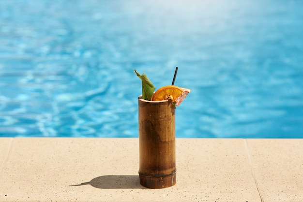 Exotic cocktail in wooden glass with lemon and drinking tube standing on poolside with blue water on background